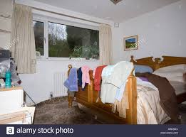 messy bedroom with clothes scattered stock photo royalty free messy bedroom with clothes scattered