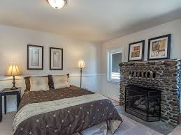 traditional master bedroom with carpet u0026 stone fireplace in