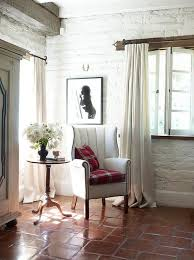 reading corner with white wingback chair and terracotta floor