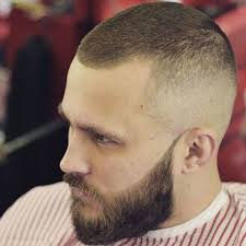 man with a 80s mullet hairstyle with shaved lines on side of head