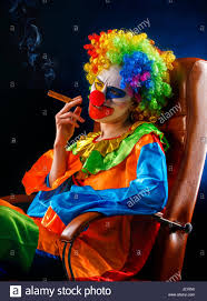 halloween clown background mad clown on black background woman is smoking cigar stock photo