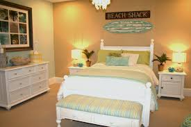 white and green bedding set on white wooden bed connected by table