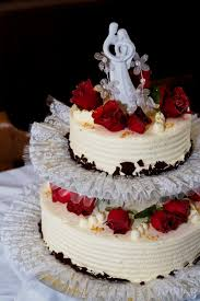 2 layered cake with red edible rose and bride and groom cake