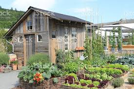 a small house made of wood with a vegetable garden stock photo
