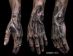 gorgeous looking black ink detailed wrist and hand tattoo of alien