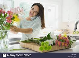 woman talking on phone in kitchen while arranging flowers stock