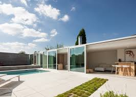 concrete and glass house extension shelters a poolside patio