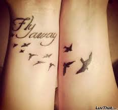 birds flying away tattoo on wrist