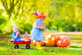 cowboy hat halloween two happy children at pumpkin patch during halloween cute curly