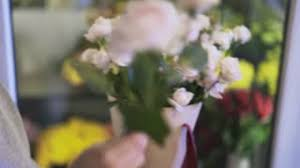 Putting Roses In A Vase Rear View Of A Woman Florist In Casual Clothes Putting Red Roses