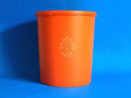 orange tupperware container with stylised flower swirl retro