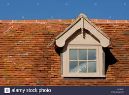 traditional style tiled roof with dormer window set against a blue