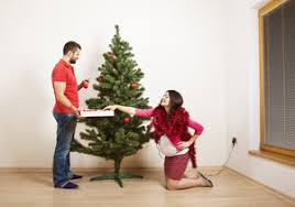 young couple is decorating christmas tree woman is pregnant