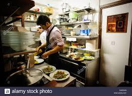 people working in a small professional kitchen la mascareta stock