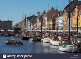 nyhavn full of old ships crowded canal tour boats and people at