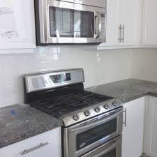 white subway tile backsplash and new caledonia granite counter in