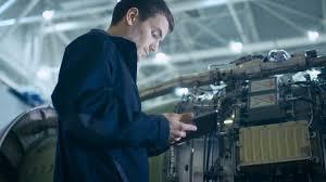 Turbine Engine Mechanic Aircraft Maintenance Mechanic Inspecting And Working On Airplane
