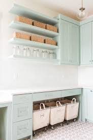 beautiful laundry room features gray green cabinets paired with white quartz countertops and a white glass