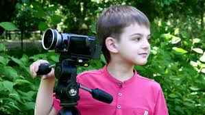 young with video camera shoots movies in nature on green park