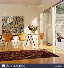 large abstract painting on wall above table with arne jacobsen ant