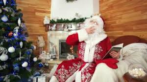 santa claus using gadget nicolas sitting in chair with