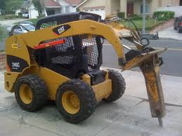 caterpillar u0027s 246c skid steer knocks away some concrete with a
