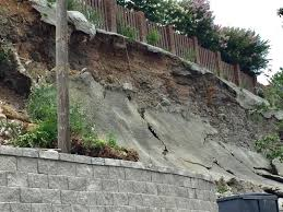 slope behind retaining wall fails near back yard burger in vesta