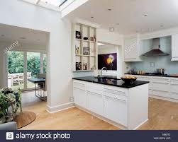 Black Granite Worktop On Peninsular Unit In Modern White Kitchen