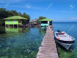 tropical resort over the water with boat at dock and bungalows