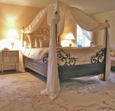 white wood canopy bed with wrought iron headboard on patterned