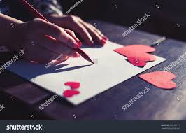 heart shaped writing paper royalty free girl write love letter for her lover on 553100131 hand made post card with heart shaped figures cut from bright red handcrafted paper woman writing on postcard for 14 february holiday