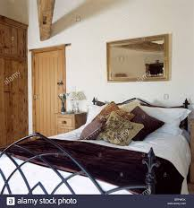 country bedroom with mirror on wall above gothic style bed with