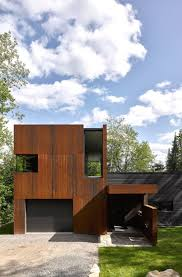 canadian lake house by paul bernier features dark wood and rusted