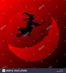 a halloween witch flying over a blood red moon stock photo