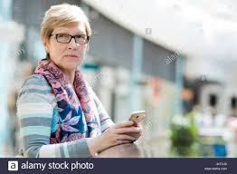 elegant mature woman elegant mature woman uses smartphone internet and social networks