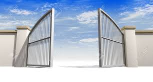 a solid garden wall with open metal gates with a blue sky in