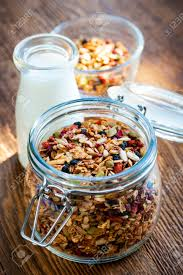 homemade granola in open glass jar and milk or yogurt on rustic