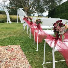 garden wedding ceremony setup with white bench seats tied with