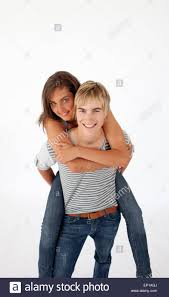 teen guy giving a friend piggyback ride stock photo royalty free