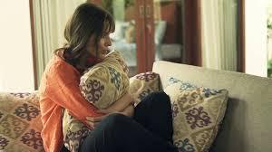 sad unhappy woman hugging pillow on sofa in outdoor villa stock