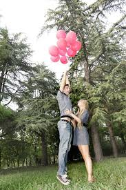 balloons for him boy is flying away with balloons girl is holding him stock