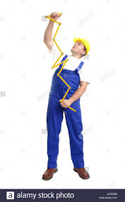 janitor jumpsuit builder wearing blue jumpsuit and yellow helmet unfolding wooden