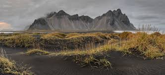 black volcanic sand dunes on the beach at stokness iceland by