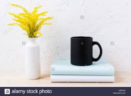 black coffee mug mockup with ornamental golden grass and books