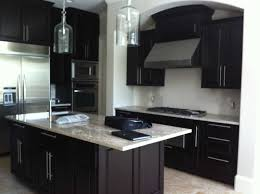 white kitchen cabinets with black island black cabinets and island dark wooden bar stools white pendant