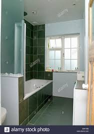 black wall tiles and glass shower panel above bath in thirties