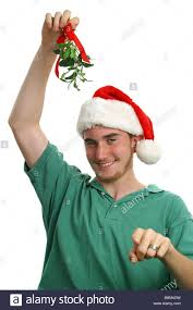 mistletoe hat a boy in a santa hat holding mistletoe and pointing toward