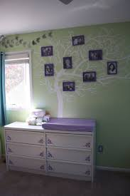 81 best nursery ideas images on pinterest nursery ideas baby hand painted tree mural with picture frames painted to match purple white and green color palette of her room it s her