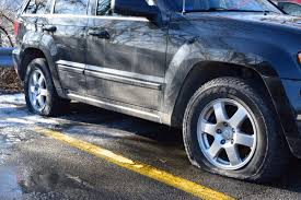 flat gray jeep car tires cut at metro north parking lot highlands current