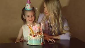 mother and daughter blow out candles on a birthday cake and making